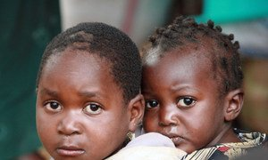 A child carries another on her back at a camp for IDPs in Nairobi, Kenya (2008).