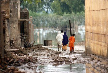 Victims of last year's floods walk the water-filled streets of the city of Nowshera