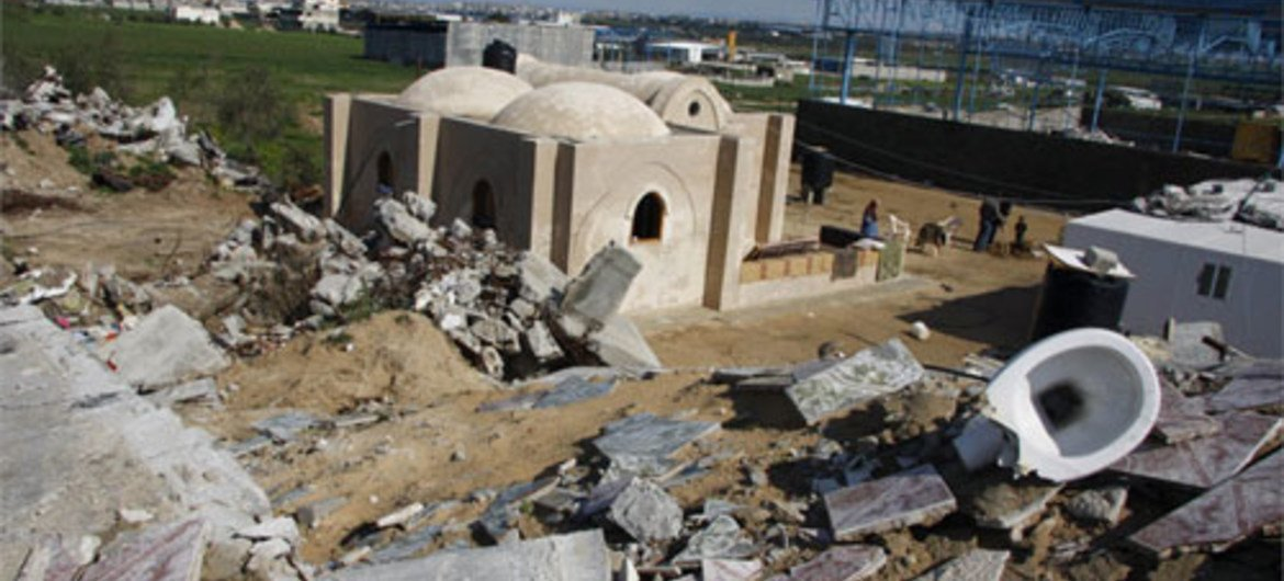 A new mud brick house stands next to the rubble of homes destroyed in the January 2009 war between Israel and Hamas
