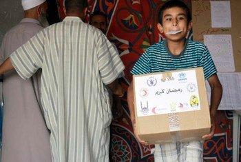 Un jeune réfugié transporte un carton de nourriture pour le repas du soir pendant le Ramadan.