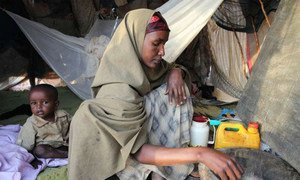 A refugee at camp Dabaad in Kenya prepares a meal for her family