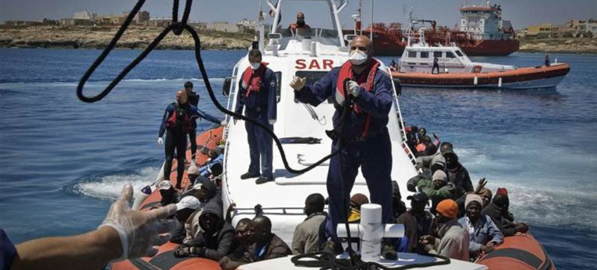 An Italian coastguard vessel, carrying 142 people rescued at sea after fleeing Tripoli, prepares to dock at Lampedusa harbour. (May 2011)