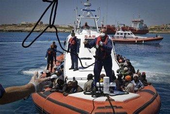 Un navire des garde-côtes italiens, avec son bord 142 personnes repêchées en mer après avoir fui Tripoli, se prépare à arriver dans le port de Lampedusa (mai 2011).