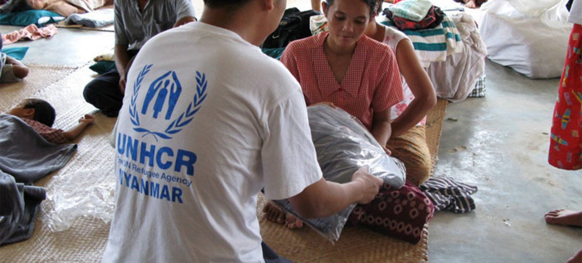 A UNHCR aid worker hands a blanket to a young victim of cyclone Nargis that hit Myanmar in 2008
