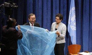 Le Secrétaire général Ban Ki-moon (au centre) déploie une moustiquaire permettant de lutter contre le paludisme. (13 septembre 2011)