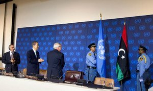 Secretary-General Ban Ki-moon (2nd left), Mustafa Mohammed Abdul Jalil (left), President of the National Transitional Council of Libya and B. Lynn Pascoe (centre) applaud as the new flag of Libya is brought in