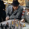Two chess players enjoying an outdoor game in New York City's Central Park.