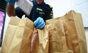 Forensic police officers examine evidence collected at a crime scene.