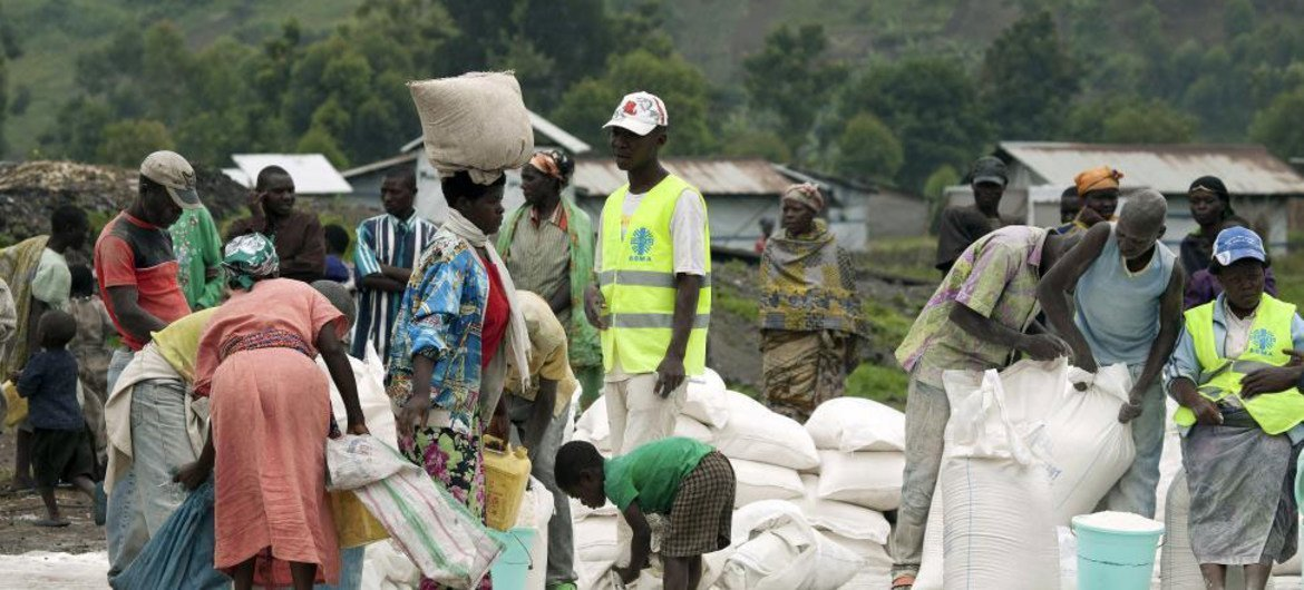 Residents of an IDP camp in North Kivu receive food rations distributed by WFP and an NGO