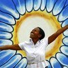 Une femme pose devant un dessin représentant le soleil. Photo