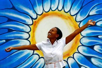 امرأة تقف أمام رسم يمثل الشمس بمناسبة الاحتفال باليوم العالمي للصحة العقلية.
