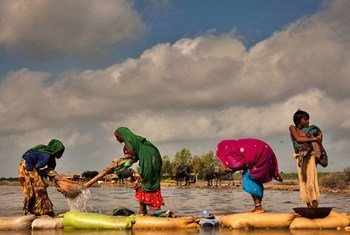 A flood-affected family in Pakistan washing clothes in rising floodwaters next to their temporary camp in Digri, Sindh province