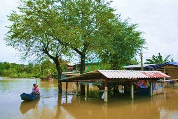 A villager manoeuvres through floodwater in Ayutthaya, north of Bangkok, Thailand