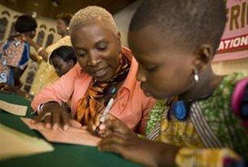 Angélique Kidjo, UNICEF Goodwill Ambassador, and a girl sign a passport in Cotonou, Benin