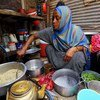 A Somali refugee cooks a meal for her family in Yemen