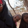 A displaced woman with two children after fleeing their home in southern Somalia.