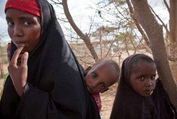 Une femme déplacée avec deux enfants après avoir fui son domicile dans le sud de la Somalie.