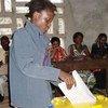 Une jeune dame vote ici au centre Anoualite à Kisangani, sous l'oeil vigilant des représentants des partis politiques