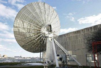 在联合国总部积雪覆盖的地面上,一个碟形卫星天线面对着东河。