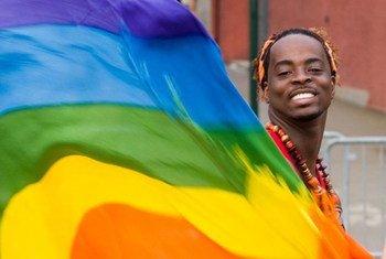 Un homme agite le drapeau arc-en-ciel, symbole international des droits des gays, lesbiennes, bisexuels et transgenres.