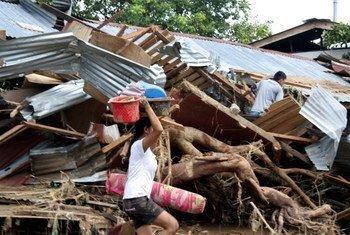 Une femme sauve des biens personnels de son village ravagée par la tempête Washi à Mindanao, aux Philippines.