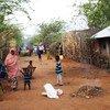 Somali refugees make their way past burning rubbish on a street at Ifo camp in Dadaab, Kenya.
