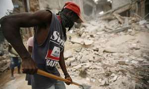 """A man employed through the """"Cash for Work"""" programme clears rubble from the streets of Carrefour-Feuilles, Haiti."""