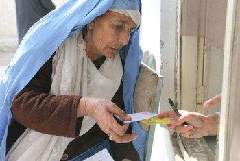 Une femme de Jalalabad reçoit un coupon-repas du PAM.