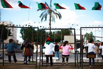 Young children play on swings in a square in Zawiya, Libya.