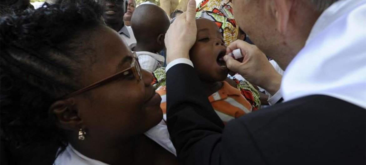 Secretary-General Ban Ki-moon administers polio medicine to a baby at a healthcare centre in Viana district, Angola in February 2012.