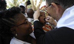 Ban Ki-moon administre un vaccin contre la polio à un bébé dans un centre de santé en Angola. Photo ONU/ E. Schneider