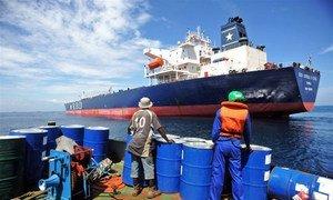 Un membre de l'équipage s'apprête à monter à bord d'un cargo restitué après son détournement par des pirates le 24 juillet 2011 au Bénin.