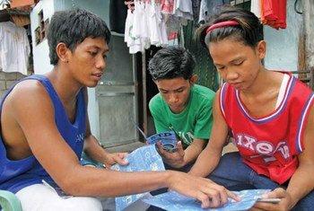 Un jeune homme explique la prévention contre le VIH/sida et d'autres maladies sexuellement transmissibles à Pasay City, aux Philippines. Photo UNICEF