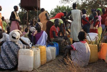 Sudanese refugees from Blue Nile state line up to collect water in a camp.