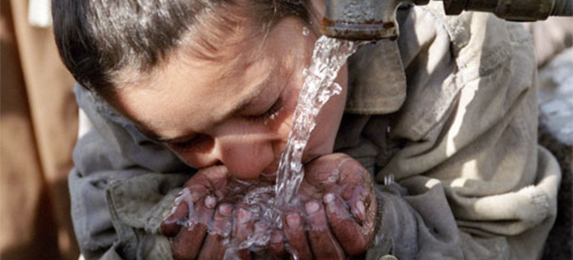 A young resident of Maslakh camp (Afghanistan) takes a drink of water.