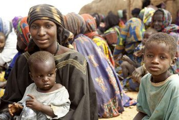 A Malian refugee mother with her children wait to receive relief items in Gaoudel, Ayorou district, northern Niger.