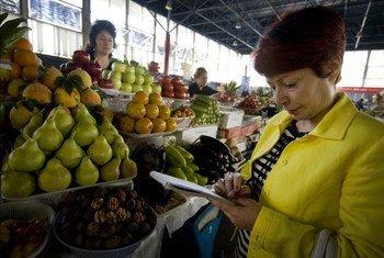 Une femme achète de la nourriture sur un marché. Photo FAO/J. Spanner