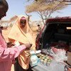 A mother buys canned fish from a local vendor using a WFP food voucher in Burao, northern Somalia.