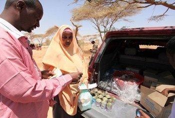 Mama akinunua samaki wa mkebe kwa vocha cha WFP Burao, Kaskazini mwa Somalia.