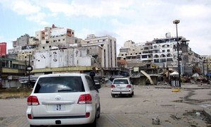 An UNSMIS delegation convoy drives througn a neighbourhood of Homs in early May.