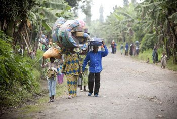 Congolese civilians carry their belongings as they escape recent fighting in Rutshuru.