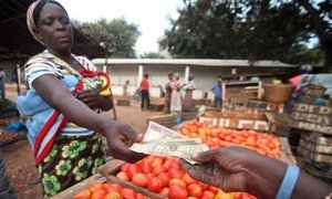 A woman purchases vegetables at a local market.