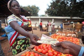 Une femme achète des tomates sur un marché local.