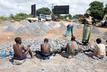 A woman watches children working at a stone quarry, Zambia. (file)