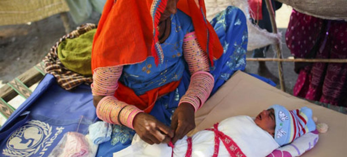 A woman swaddles her crying newborn in a camp in southern Pakistan.