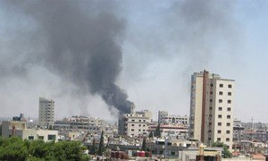 Smoke drifts into the sky from buildings and houses hit by shelling in Homs, Syria (June 2012).