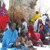 A group of colourfully dressed women with their children after arriving at the Yusuf Batil settlement in Upper Nile state, South Sudan.