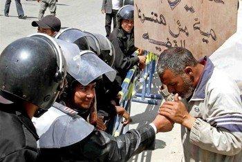 """Des militants manifestent contre les brutalités policières en Egypte. L'un d'entre eux brandit une pancarte sur laquelle est écrit: """"Votre travail est nous protéger, pas de nous torturer."""""""