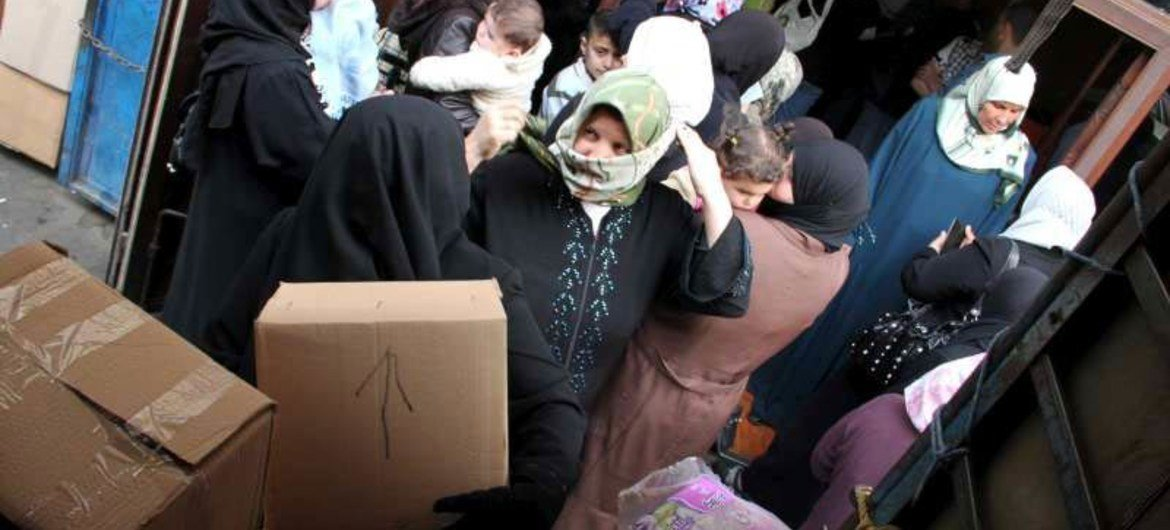 Syrian refugees receive supplies from UNHCR in northern Lebanon.