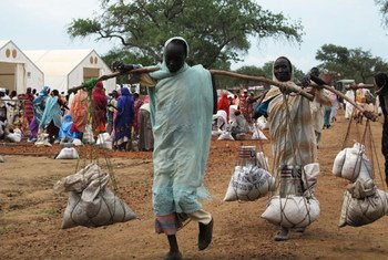 Women return to shelters after receiving food assistance provided by WFP at Yusuf Batil refugee Camp.